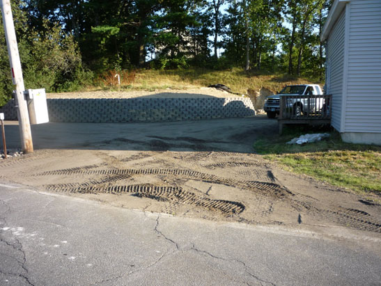 View Excavate, Prep, and Install a Block Retaining wall around a leech field in Plaistow, NH.  Spread, Grade, and Roll recycled asphalt driveway around the files