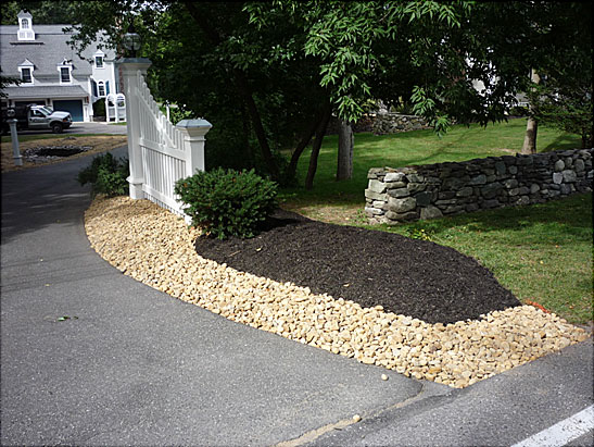 View Excavate and Install Multi-Tan stone along a driveway in Newbury, MA.  Clean out brush and install Dark Bark mulch behind the multi-tan stone files